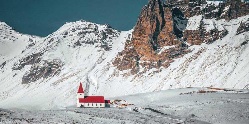 IJsland-kerkje-omringd-door-besneeuwde-bergen
