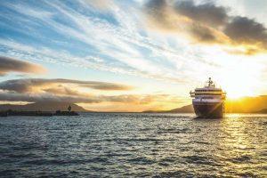 Hurtigrutenschip-bij-ondergaande-zon-op-Hurtigruten-zeereis-met-Nordic-300x200