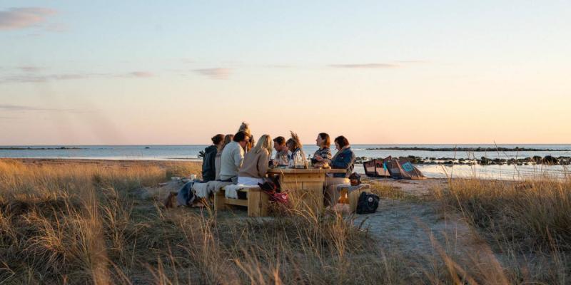 Mensen dineren aan een tafel in de natuur