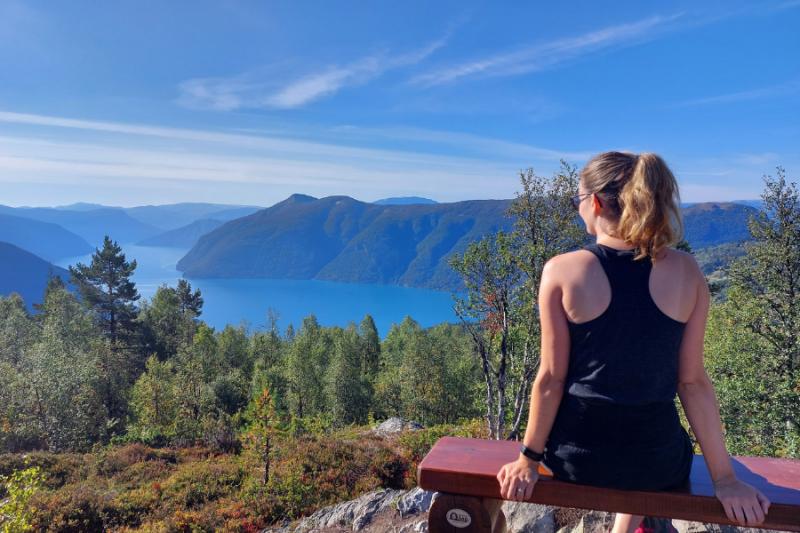 Zittend op een bankje op de top van Mount Molden met uitzicht over helderblauw water in de fjord.